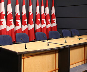 Conference table with row of Canadian flags