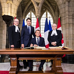 H.E. Emmanuel Macron, President of the French Republic, signing the Distinguished Visitors' Books at the Parliament of Canada in the presence of Canadian PM, Justin Trudeau, Senate Speaker, George Furey, and House of Commons, Speaker Geoff Regan.  June 6, 2018.